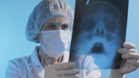 Old female doctor looking at an x-ray wearing face mask