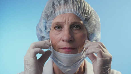 Old female doctor puts on an N95 mask
