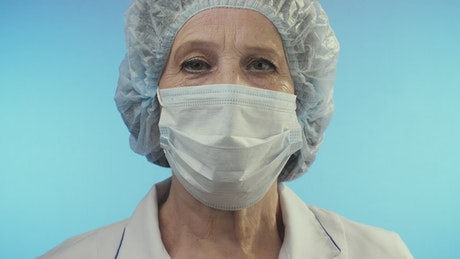 Old female doctor wearing face shield from surgery