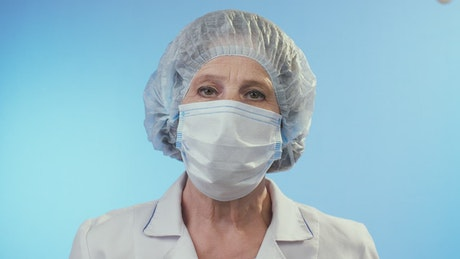 Old female doctor wearing surgery clothes and mask