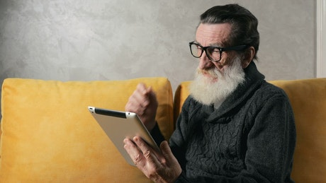 Old man answers mobile phone call while on tablet at home