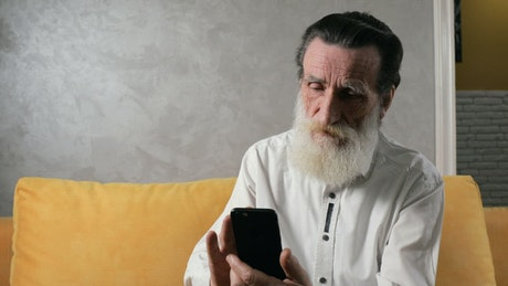 Old man taking successfully takes selfie with mobile phone