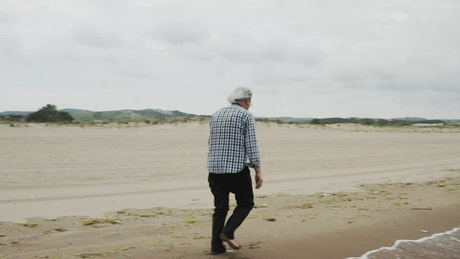 Old man walking by the shore