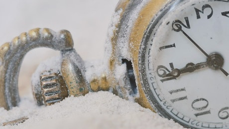 Old pocket watch on snow
