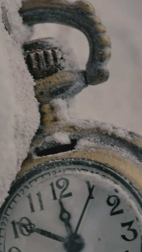 Old pocket watch thrown in the snow