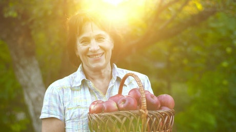 Old rancher woman holding a basket with apples