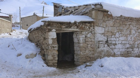Old rock house covered in snow