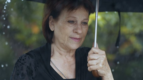 Old sad woman at a funeral while raining