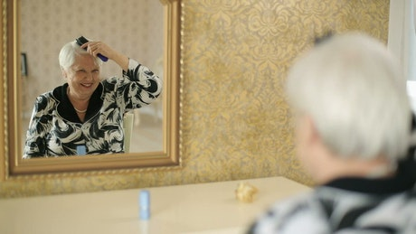 Old woman combing her gray hair