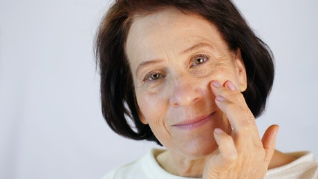 Old woman massaging skin on her face