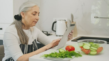 Old woman searching for healthy recipes