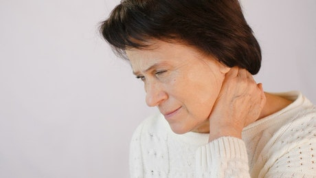 Old woman sore her neck from tension