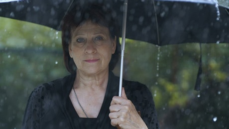 Old woman with umbrella while it rains at a funeral
