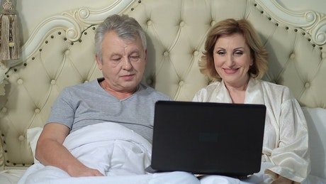 Older couple chatting on a laptop