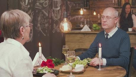 Older couple enjoy romantic dinner date