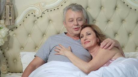 Older couple hugging in bed