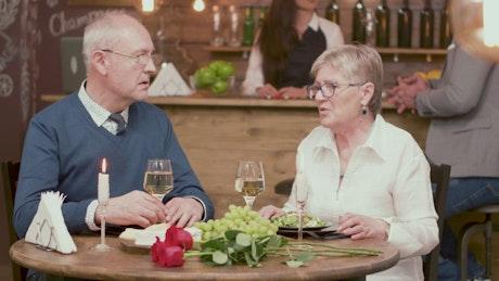 Older couple talk romance in vintage wine bar