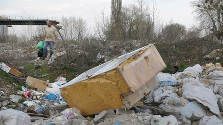 Older man searching a waste site