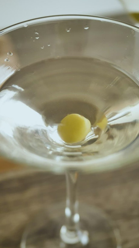 Olive falling into a martini glass