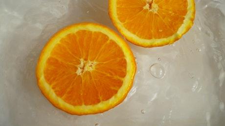 Orange half spinning while floating in water
