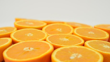 Orange halves spinning with a white background