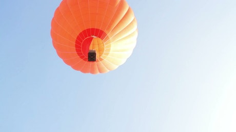 Orange hot air balloon flying