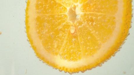 Orange slice dipped in a soda