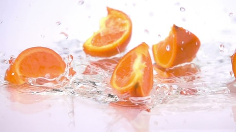 Orange slices falling into water
