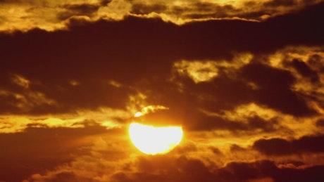 Orange sunrise against black clouds