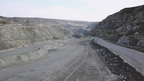 Orange truck heading through a quarry