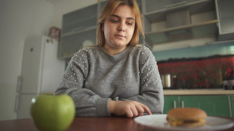 Overweight woman chooses apple over cheeseburger