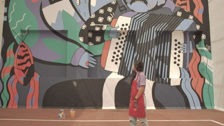 Paint covered woman stands in front of mural