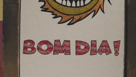 Painted sign on a building with the words Bom Dia!