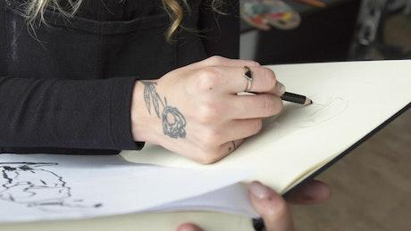 Painter draws in sketchbook in art studio