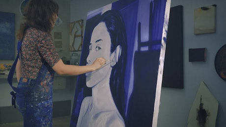 Painter working on a portrait in blue tones
