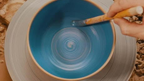 Painting a spinning pot blue using a brush
