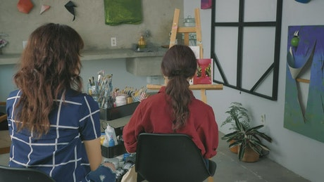 Pair of artist girls working together on a painting