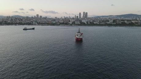 Pair of cargo ships sailing near a coastal town