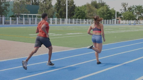 Pair of man and woman athletes running on a track