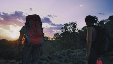 Pair of mountaineers leaving through nature at sunset