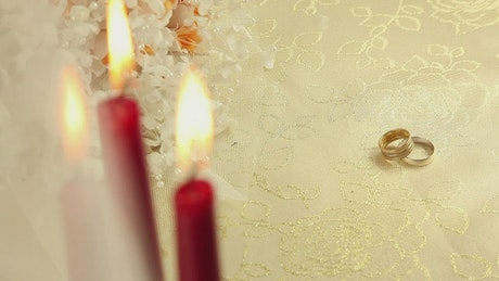 Pair of rings beside plastic flowers and candles