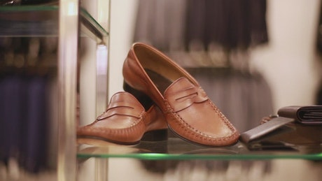 Pair of shoes on a sideboard are taken by a man