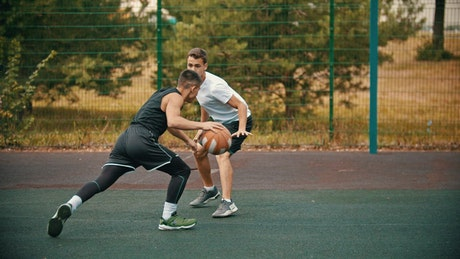 Pair of young men playing basketball in a park