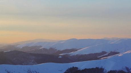 Pan shot of a stunning sunset in winter mountains