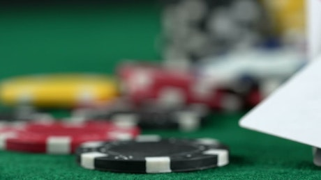 Panning shot of a casino board with dice and poker cards