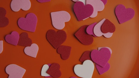 Paper shape hearts on an orange surface