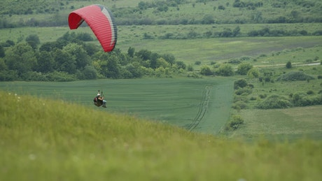 Paraglider floats over green countryside