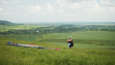 Paraglider lifts off over open field