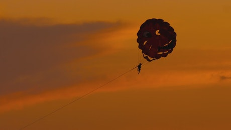 Parasailing in an orange background sky