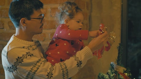 Parents and daughter putting a bow on the top of the Christmas tree